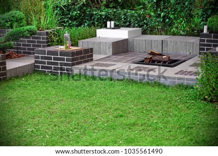 Backyard Party Or Family Area With Open Iron Fireplace And Stationary Furniture Made From Bricks, Wood And Stone Tiles. Modern Garden Landscaping Concept And Idea