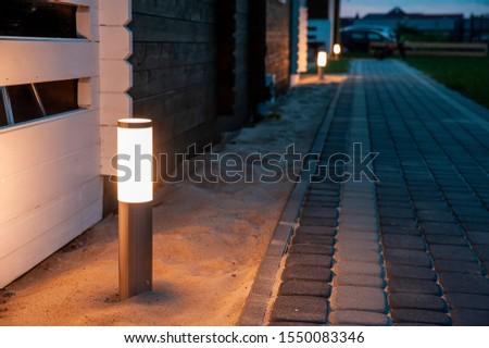 Backyard sidewalk illumination at dusk