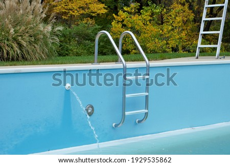 backyard swimming pool with pool slide and ladder emptied out shutting down for winter ストックフォト ©