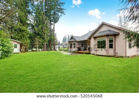 Backyard view of luxury home with well kept lawn on a rainy day. Northwest, USA