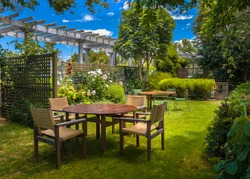 Backyard with garden table set in sunny a lush garden with shade of trees on a summer day