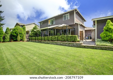 Backyard with gazebo, view of beautiful landscape design with lawn and trimmed hedges