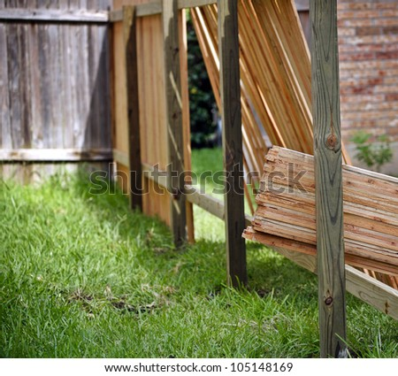 Backyard with lumber for new privacy fence, old fence and partially built new fence - stock photo