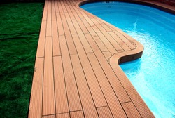 Backyard with swimming pool and composite material brown deck and blue water