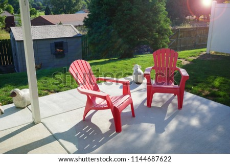 backyard with two Adirondack chairs and bright sun and lens flare
