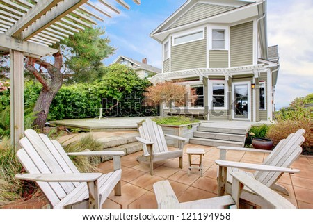 Backyard with white chairs and tall old home during spring.