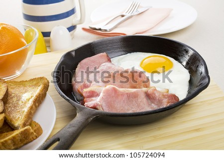 Bacon and egg breakfast in a cast iron frying pan, and a plate of toast.