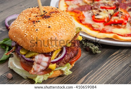 bacon cheese burger with beef patty tomato onion and pizza on a wooden table