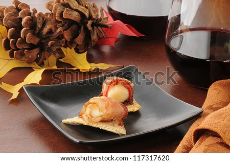Bacon wrapped scallops on wheat crackers with red wine
