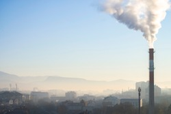 Bad air pollution in the city with factory chimney producing big white smoke. Cityscape covered in smog.