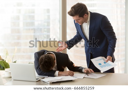 Bad angry boss yelling at male sad depressed employee, lying with face down on office desk, ineffective worker made mistake receiving reprimand from team leader, scolding for failure, missed deadline
