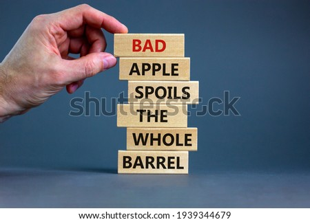 Bad apple spoils the whole barrel symbol. Wooden blocks with words 'bad apple spoils the whole barrel'. Businessman hand. Beautiful grey background. Business, popular quotation concept. Copy space. Photo stock ©