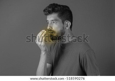 Bad breath. Halitosis concept. Young man checking his breath with his hand.