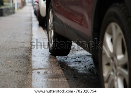 Bad car parking with part of the rear tyre on the pavement