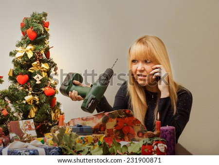Bad Christmas gift makes the pretty girl look disappointed in x-mas time under the christmas tree.