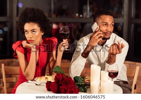 Bad Date. Bored African American Girl Waiting While Boyfriend Talking On Phone Having Dinner In Restaurant. Photo stock ©