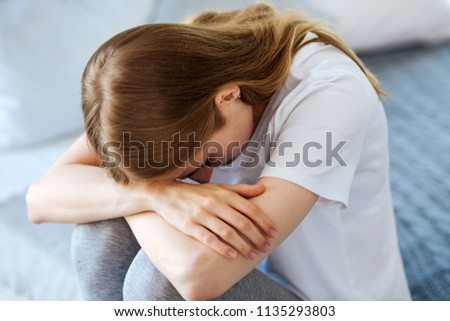 Bad day. Miserable fair-haired woman sitting and crying and having her head down #1135293803