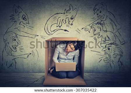 Bad evil men pointing at stressed woman. Desperate scared businesswoman hiding in a box working on laptop grey office wall background. Negative human emotions face expression feelings life perception