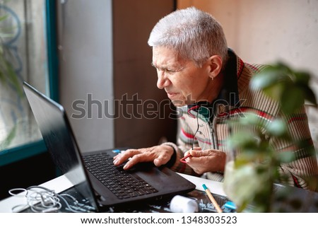 Bad eyesight for a senior older woman, grandma sitting in a coffee shop can't read text on her laptop
