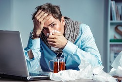 Bad feeling. Sick worker has high temperature. Photo of young man in office suffering virus of flu. Medical concept.