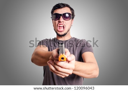 bad guy with gun on grey background