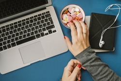 Bad habit. Work space with laptop, candy, chips, water and apple and woman hands on blue background. Top view