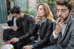 Bad habits - group of young friends smoking cigarettes together outdoors. Unhealthy addiction concept.