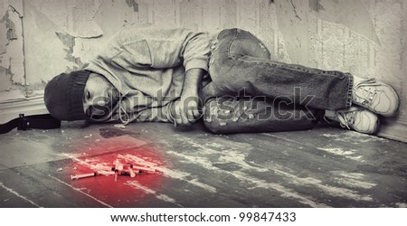 bad man - addict  with a syringe using drugs  lying on the floor