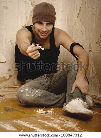 bad man - drug dealer with syringes and  with drugs sitting on the floor
