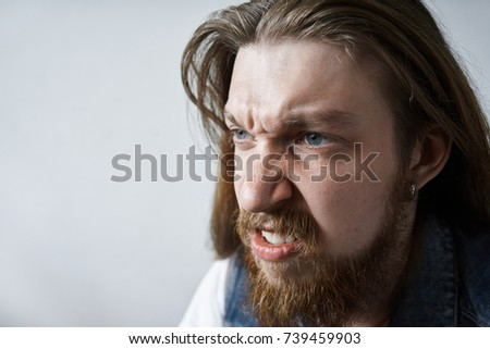 Bad mood, anger and fury concept. Angry blue eyed man with long haircut, earring and fuzzy beard roaring and clenching fists while feeling mad at someone, his look and grimace expressing rage #739459903