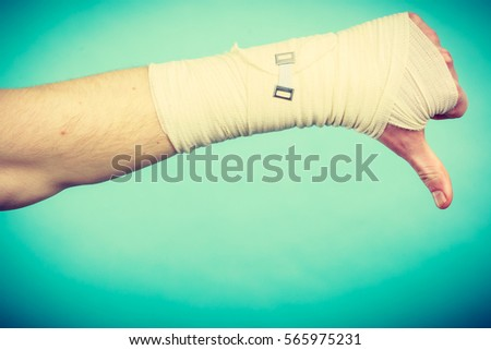 Bad news and information. Medicine aspects. Male hand with bandage showing thumb down sign symbol. #565975231