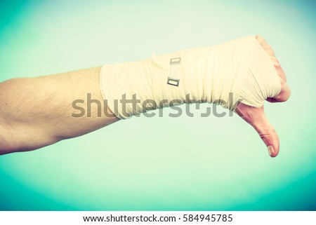 Bad news and information. Medicine aspects. Male hand with bandage showing thumb down sign symbol. #584945785