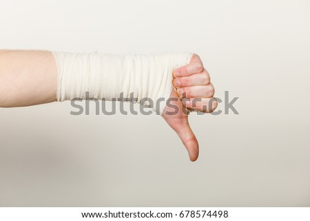 Bad news and information. Medicine aspects. Male hand with bandage showing thumb down sign symbol. #678574498