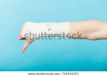 Bad news and information. Medicine aspects. Male hand with bandage showing thumb down sign symbol. #724456351