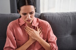 Bad news. Stressed young woman feeling pain and touching chest suffer from heartache disease at home while having heart attack, infarction