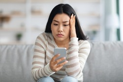 Bad News. Upset Asian Female Holding Smartphone, Looking At Mobile Phone Screen With Worry While Sitting On Couch At Home, Anxious Korean Woman Touching Head While Reading Unplesant Message, Closeup