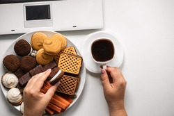 Bad nutrition habits, overeating concept. Woman eating cookies at workplace. Young girl snacking with big portion of sweets and junk food