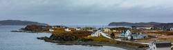 Bad rainy weather at North Atlantic Ocean shoreline with traditional outport fishing town houses of Twillingate, Newfoundland, NL, Canada
