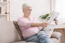 Bad sight problem. Senior lady squinting and holding newspaper far from eyes at home, free space