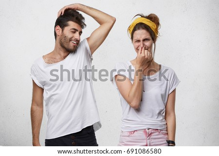 Bad smell and body odor. Picture of fastidious young woman pinching her nose disgusted with terrible sweat, coming out from bearded man's armpit who is standing next to her, raising his arm
