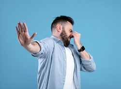 Bad smell concept. Young bearded guy closing his nose and showing STOP gesture, expressing disgust on blue studio background. Millennial man repulsed by toxic odor or terrible perfume