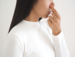 bad smell in nose in asian woman and cause of nasal polyps or sinus infection and post nasal drip on white background use for health care concept.