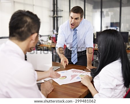 bad-tempered caucasian business executive yelling at two asian subordinates in office.