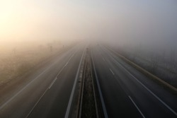 Bad weahter photography. High angle view of driving on a gray foggy day on the highway. Low visibility condition. Difficult and dangerous hazard for drivers. Drive safely in autumn and in winter.