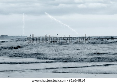 bad weather in winter on the sea with lightning at horizon