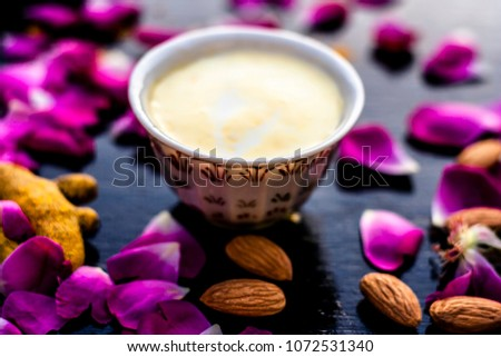 Badam, Haldi & milk ubtan or ayurvedic face mask's ingredients with ready face pack of Almond with turmeric powder on a black surface removes the dull and black skin.