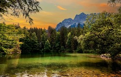 Badersee and View to the Waxenstein Mountain. Trees and Colorful foliage on the shore of Lake Bader. Idyllic landscape scene with Tree reflections in Idyllic and calm pond water. Bavarian alps