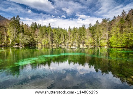 Badersee in bavaria with small hotel on the lake between mountains of Alps