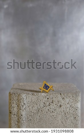 Badge of Freemasonry on a stone surface. The masonic square and compass symbol. Copy space. Vertical image. Stock photo ©