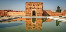 Badi Palace in Marrakech with reflection in water pond in front and tourists in the background